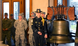 A Connecticut State Trooper rings the bell at the State Capitol Friday morning to honor Sandy Hook victims while National Guardsmen look on. Photo courtesy of Christine Stuart, www.ctnewsjunkie.com.