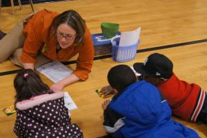 First-grade teacher Stefanie Donahue works with students on an activity based on a Clifford book they've just read together.