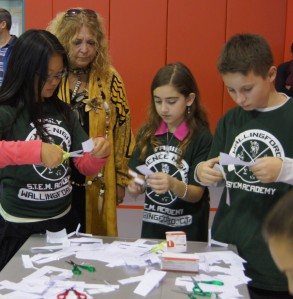 Wallingford STEM Academy students show CEA President Sheila Cohen how to make paper helicopters.