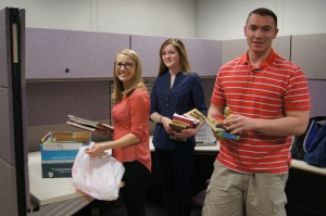 CCSU students Bryanna Novak-Rich, Kelly Barr, and Bryan Czel sorted books by grade level to prepare them for delivery to Mayberry School in East Hartford and Waterbury's Hopeville Elementary School