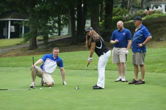 Ashford teachers Chris Moore, chris Busse, and mark Phelps watch as Jennifer Wood sinks a putt on the 6th green.
