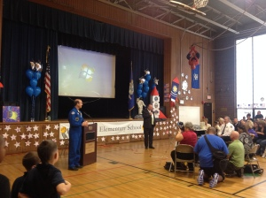 Astronaut Rick Mastracchio stands at the podium while Waterbury Mayor Tim x welcomes the crowd to Chase Elementary School.