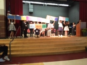 TAG students held up signs they designed to advocate for the program that encourages and engages them.
